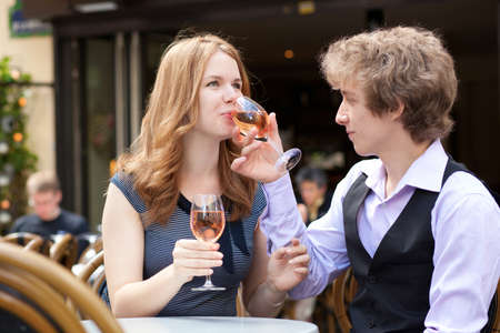 Romantic couple drinking pink wine in a cafe photo