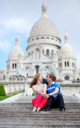 Couple of tourists sitting by the Sacre-Coeur in Paris Stock Photo - 13792197