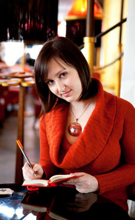 brune: Beautiful young woman planning her day in a cafe