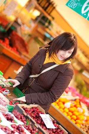 brune: Beautiful young woman buying cherries at market