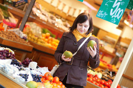 Beautiful young woman buying mangoes at market Stock Photo - 13998120