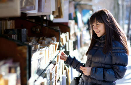 brune: Beautiful woman in Paris selecting a book in an outdoor bookseller box