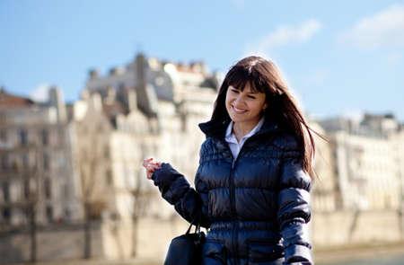 brune: Happy brunette girl walking at Parisian embankment in Paris