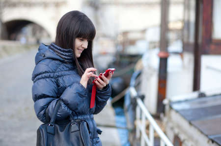 Happy beautiful brunette tourist in Paris sending an sms to a friend photo