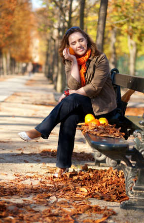 Beautiful young woman with oranges in park at fall photo