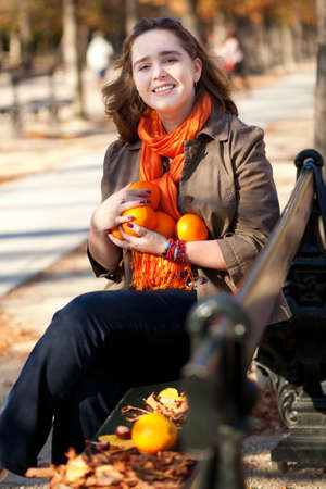 jardin de luxembourg: Beautiful young woman with oranges in park at fall