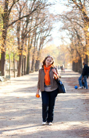 Beautiful young woman with orange in park at fall photo
