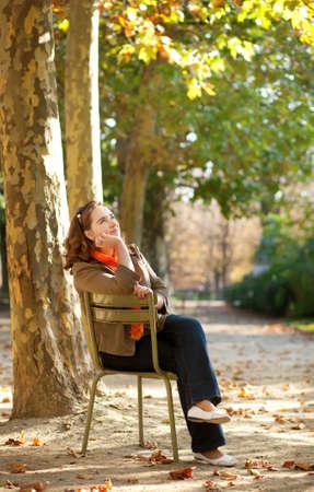 jardin de luxembourg: Beautiful young woman enjoying warm autumn day Stock Photo