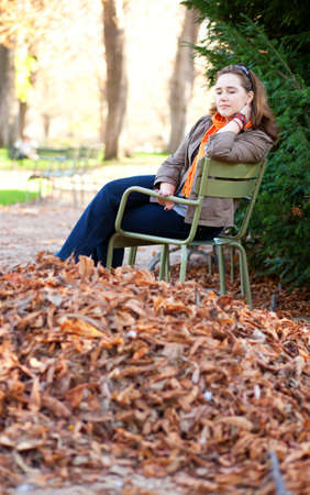 Thoughtful young woman enjoying warm autumn day in park photo