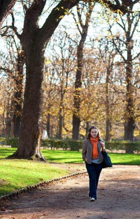 Beautiful young woman enjoying warm autumn day in park photo