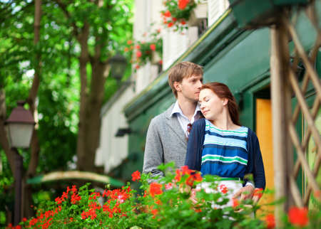 Man and woman together on balconyof their house or hotel with blossoming geranium and nice view photo