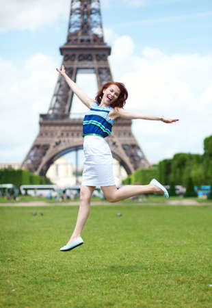 Happy beautiful girl jumping near the Eiffel Tower in Paris photo