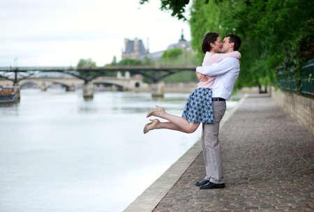 luna de miel: Feliz pareja rom�ntica est� abrazando a orillas del Sena, ni�a est� saltando Foto de archivo