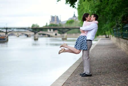 adult dating: Happy romantic couple is hugging near the Seine, girl is jumping