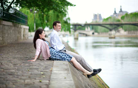 Joyful couple is sitting on the embankment photo