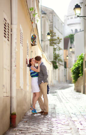 Romantic couple kissing on a street of Montmartre in Paris photo