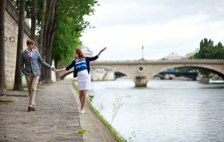 Couple is walking by the Seine embankment in Paris, girl is balancing on the water edge photo