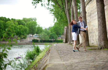 Happy couple is dancing on the Seine embankment in Paris