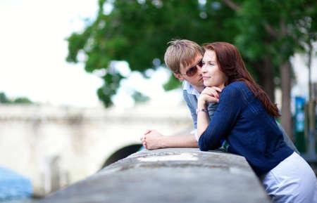 Romantic couple is talking at the Seine embankment in Paris photo