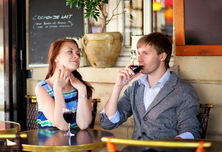 Beautiful couple drinking red wine in a French cafe photo
