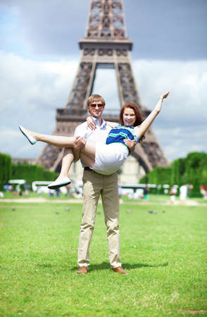 Closeup of happy positive couple having fun near the Eiffel tower photo