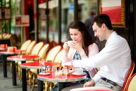 マカロン: パリの屋外カフェでコーヒーを飲んで幸せなカップル