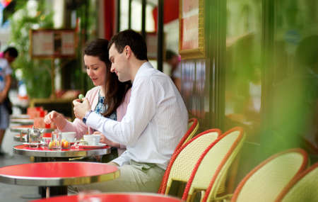restaurant food: Happy couple eating macaroons in a Parisian outdoor cafe
