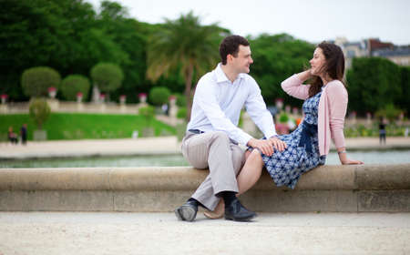 jardin de luxembourg: Romantic couple sitting by the water in Luxembourg garden of Paris