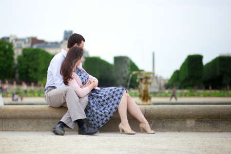Romantic couple sitting by the water in Luxembourg garden of Paris