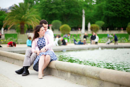 jardin de luxembourg: Loving couple sitting by the water in Luxembourg garden of Paris