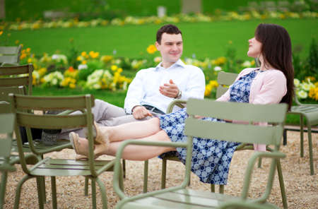 jardin de luxembourg: Laughing couple sitting on chairs in Luxembourg garden of Paris