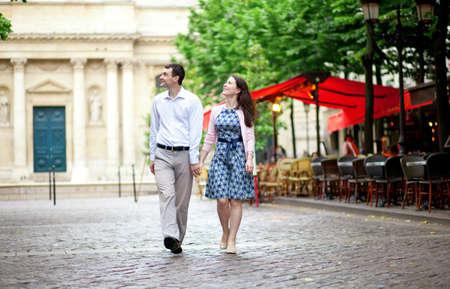 Couple walking in Paris near a street cafe photo