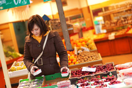 brune: Beautiful young woman buying fruits at market Stock Photo