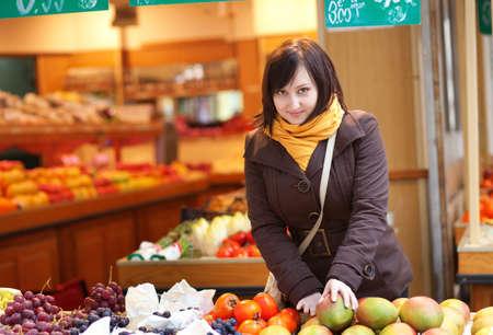 brune: Beautiful young woman selecting fresh mangoes at market Stock Photo
