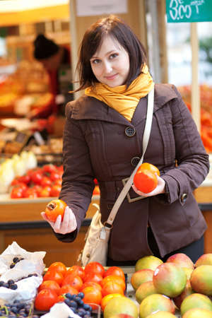 brune: Beautiful young woman selecting date plums at market Stock Photo