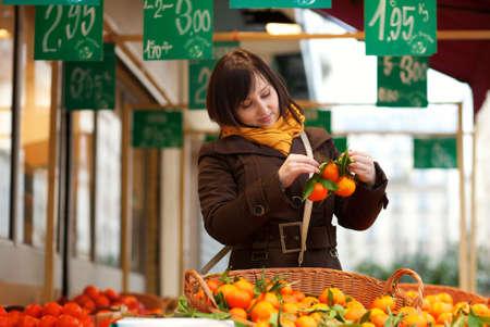 brune: Beautiful young customer selecting tangerines at market