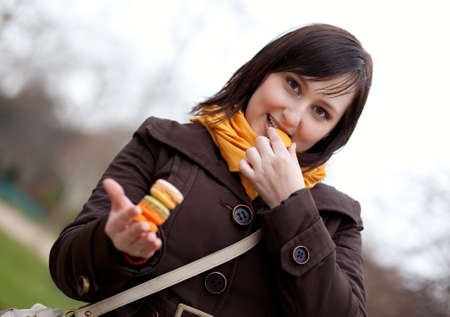 brune: Happy young woman eating macaroons