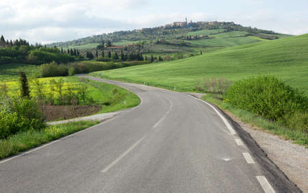 Winging road and town of Pienza on the hill. Tuscany, Italy photo