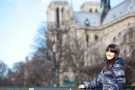 brune: Happy beautiful brunette tourist in Paris near Notre-Dame de Paris Stock Photo