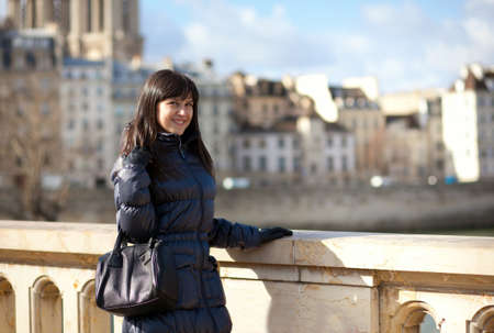 brune: Smiling brunette tourist on a bridge in Paris Stock Photo