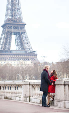 Romantic couple in love dating near the Eiffel Tower in Paris photo