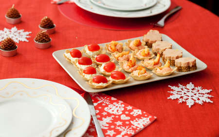 Decorated Christmas table with plate of tasty tartlets (cheese, tomatoes, seafood and foie gras) photo