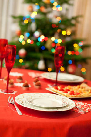 Decorated christmas dining table with champagne glasses and christmas tree in background  photo