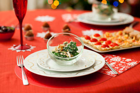 restaurant setting: Decorated Christmas dining table with delicious salad (spinach, pear, blue cheese and pine tree nuts)