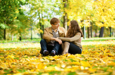 Young man and woman in a park by fall Reklamní fotografie - 15763158