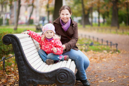 Smiling mother and daughter sitting on a bench photo