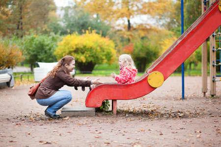 Moeder en dochter met plezier samen op speelplaats Stockfoto