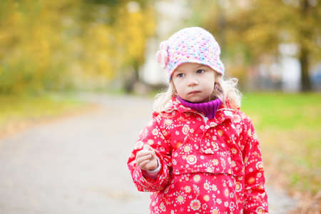 Outdoor autumn portrait of thoughtful little girl photo