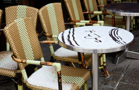 Valentines day n Paris - table of Parisian street cafe covered with snow and heart drawing on it photo