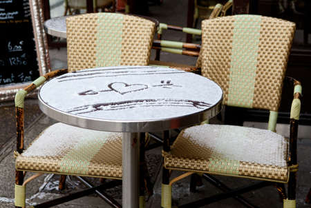 Table of Parisian street cafe covered with snow and heart shaped drawing photo
